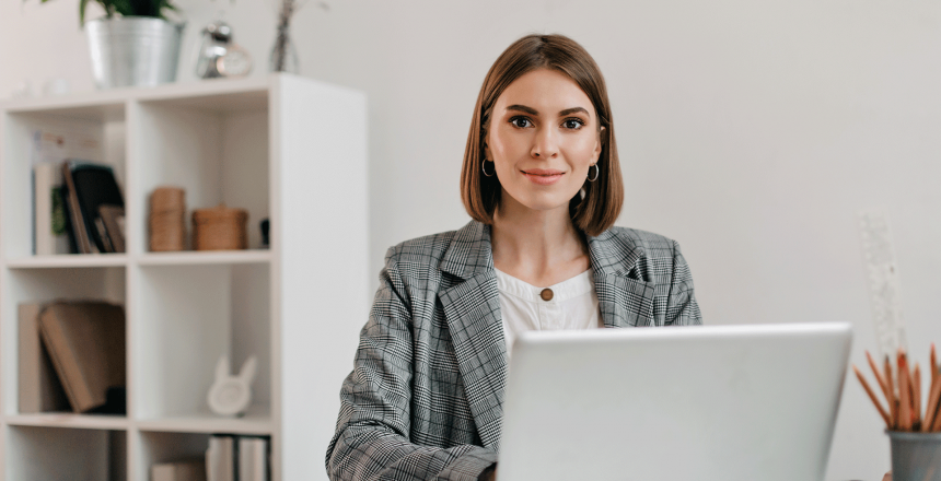 business-woman-in-checkered-jacket-with-smile-while-sitting-at-desk-in-her-office