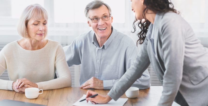 Insurance Concept. Happy senior couple consulting with female agent at office, signing papers
